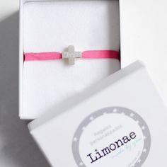 Pulsera cruz cuadrada de plata. Pulsera en cinta elástica rosa, muy fácil de poner y de quietar con cruz con volumen de plata de forma cuadrada. Pulsera personalizada con el nombre de la niña. Ideal como regalo de Primera Comunión. Presentación de regalo. Precio: 26 €