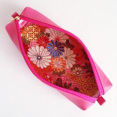 The pen case is made from pink leather with brocades of chrysanthemum pattern.