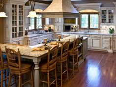 This kitchen combines a soft French country look with modern convenience. An L-shaped island keeps traffic in the cooking area to a minimum.