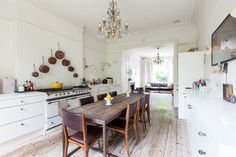 An all-white London kitchen with glamour accents. A pyramid of copper pots, an antique chandelier, a farmhouse table, and leather dining chairs. Wide plank wood floors.