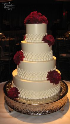 4 Tier wedding cake accented with red flowers and white beads.