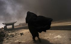 An Iraqi woman walks through a plume of smoke rising from a massive fire at a