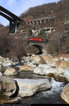 """Train IR 2165 from Zürich to Locarno with locomotive Re 460 118 is crossing the Ticino river on the lowest level of the """"railway staircase"""" of the Gotthard line in the Biaschina, while train IR 2280 in the opposite direction from Locarno to Zürich with Re 460 081 is crossing the Pianotondo viaduct on the uppermost level. This is a compilation of two shots taken 50 seconds apart."""