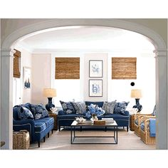 Love the architectural detail of the arched pass through...casual room with a nice added texture in the rattan furniture and match stick blinds.