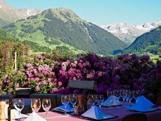Nestled among the rolling peaks of the Bernese Alps, HUUS' sunny hillside location boasts the best views in all of Gstaad, Switzerland. Switzerland Hotels, Alps, Nice View, Patio, Outdoor Decor, Flowers, Travel, Yard, Trips