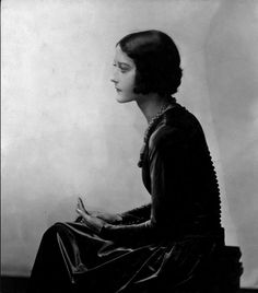 Seated woman in profile wearing richly detailed dress 1928