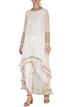 Featuring an off white asymmetrical kurta in georgette base with sequins cheetah hand embroidery, frills and mirror border. It is paired with matching dhoti pants and inner in crepe base. Indian Fashion Designers, Indian Designer Outfits, Designer Dresses, Designer Clothing, Designer Wear, Kurti Designs Party Wear, Pernia Pop Up Shop, Indian Ethnic, Indian Style