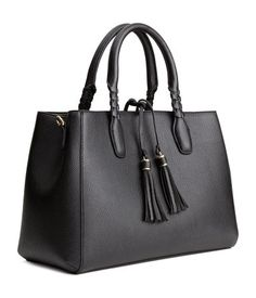 Handbag in thick, grained imitation leather. Two handles with braided details, detachable shoulder strap, ties with tassels, and magnetic fastener at top. Two large compartments, central compartment with zip, and three inner pockets, one with zip. Lined. Size 5 1/2 x 10 1/2 x 13 3/4 in.