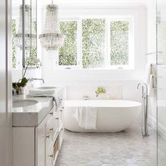 """Love this #largescale #hextile for the floor! Way better than 12x24 #charcoaltile which is way overused right now with the #greytrend if the 2"""" #whitehex is too expensive to install this is a great #classic and #timeless alternative! #freestandingtub #marblecountertops #whitebathrooms #angelslivehere #crystalchandelier image via @veranda"""