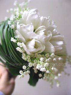 White Tulips with hints of lilly of the valley floral & stems wrapped in bear grass