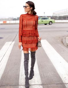 A lace ruffled dress with over-the-knee boots.
