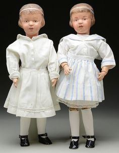 "Both dolls have the impressed markings in the back of torso, and both are of the identical mold number however one has a pink hair ribbon and the other blue. Both have been well redressed in 1910 style clothing; the shoes are new. SIZE: Both are 19"" t (49cm). PROVENANCE: The Madelyn Trotter Collection. CONDITION: Both dolls have some paint touch up on the faces especially the doll with the blue ribbon. Paint on bodies appears to be original. 1-14450, 1-14451"