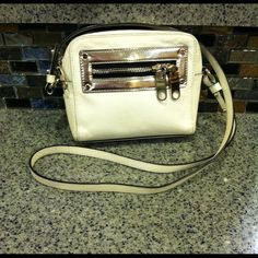 MILLY White Leather Bag Gently used, white leather bag/ cross body bag. The out side of bag has a pocket on each side, one side has a zip close pocket. The inside of the bag is roomy and also has a pocket on each side, one is a zip close. Cute bag only used a few times, still in good condition. Milly Bags Crossbody Bags
