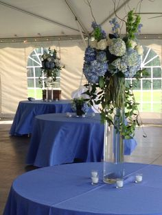 Tall centerpiece of blue hydrangeas and white roses, the island house