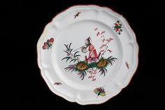 Assiette à bord argenterie, décor polychrome d'un chinois fin une canne à pêche sur l'épaule, marchant sur une terrasse fleurie avec haie. Insectes sur l'aile. Lunéville, Fin XVIII°S. D : 25 cm