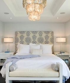 Gorgeous ivory & blue master bedroom design with cream & blue custom headboard, glossy white lacquer nightstands, crisp white bedding, white modern bench with ivory velvet cushion, crystal lamps with square lamp shades with gray ribbon trim, soft gray blue walls paint color and capiz chandelier.