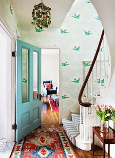 Bright nature-inspired entryway with a vintage rug, and a printed wallpaper