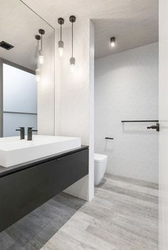 Creating A Minimalist Bathroom \/\/ Create Contrast --- Even though the walls should be kept fairly light bringing in darker elements like black hardware can make a bold statement without bringing in unnecessary objects.