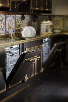 butler's pantry by Officine Gallo (Italy) featuring twin dishwashers, a brass faucet and countertop, and a backsplash of tile medallions.