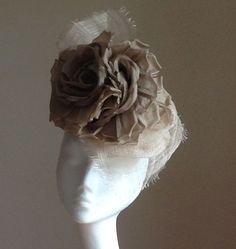 Antique gold silk flowers on a sinamay base. www.ajhats.co.uk