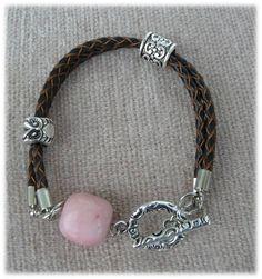 R94 - Pulseira em cabedal castanho, 2 peças e fecho metálico, conta com formato quadrado rosa.  4,30€