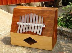 MARIMBOL  El marimbol , marímbula o marimba es un instrumento musical idiófono. Consiste en una serie de placas de metal, sujetas en un lado, que al pulsarlas por un extremo libre, producen una nota musical. Están adheridas a una caja de madera como resonador. Es un instrumento lamelófono. Cigar Box Guitar, Piano, Musical Instruments, Cuba, Ideas, Licence Plates, Music Notes, Wood Crates, Guitar