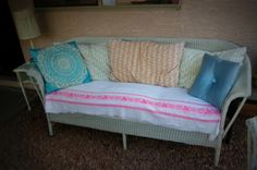 Antique wicker couch and rocker with vintage feather bed pillows and vintage throw pillows!