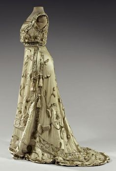 Evening dress, attributed to Maison Worth, ca. 1900. Ivory tulle net embroidered in gold and ivory silk in large trapunto-embossed abstract patterns, friezes of shamrocks and thistles. Two panels in skirt flare and close on the sides with fringed silk tassels.
