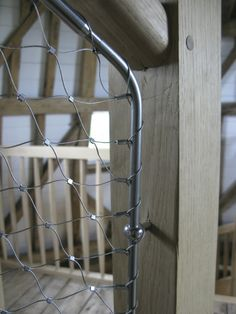 Stainless steel netting on the wooden spiral staircase.