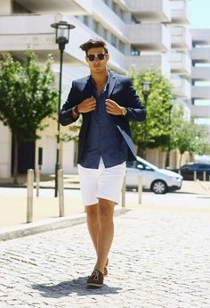 Shop this look on Lookastic: http://lookastic.com/men/looks/sunglasses-blazer-watch-long-sleeve-shirt-shorts-oxford-shoes/10420 — Black Sunglasses — Navy Blazer — Gold Watch — Navy Long Sleeve Shirt — White Shorts — Brown Suede Oxford Shoes