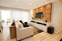 O piso laminado de madeira reveste quase todo o apartamento. Na sala, ele harmoniza tapete, estampado com mandalas, nas cores bege, preto e marrom.