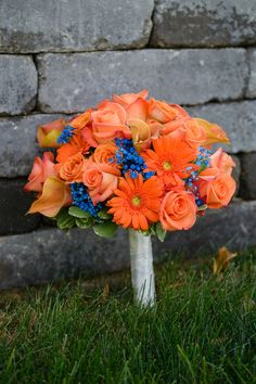 Orange bouquet with pops of blue Photo By Everlasting Love Photography