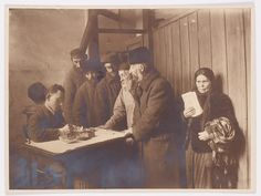 Warsaw. HIAS staff workers at work processing emigrants; woman holding papers is on the right; writing implements are on the table. One of over 100 photographs taken by Kacyzne to document HIAS' emigration aid activities.