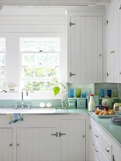 bead board cabinets. love the counters. Cabinets from the 1930s get an easy update with the addition of bead-board doors plus new, modern knobs and pulls. (from Country Living)