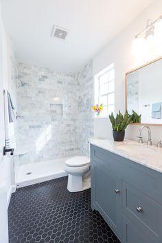 Carrara Marble tile shower surround. Black hex tile. Gray vanity with Carrara marble top, wide spread faucet. White Oak mirror, Milan hardware.