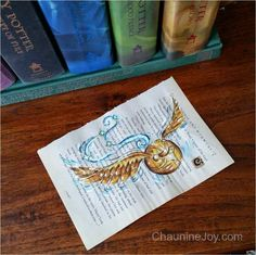 The Golden Snitch - Painted on a book page from Harry Potter and the Chamber of Secrets by Artist, Chaunine Joy