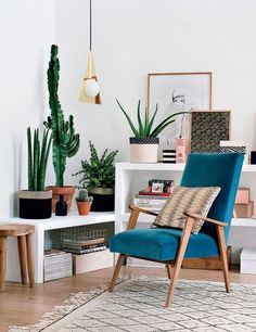Ce petit coin salon est une grande réussite avec ses touches de bois et beaucoup de plantes rehaussés par un fauteuil années 50 bleu canard en velours
