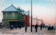 People in Japanese and Western style dress walk on the pier in Yokohama Harbor. A steamship can be seen in the back, spewing black smoke from its smokestack. The red brick building in the back housed the Yokohama Customs Office Inspection Bureau and was built in 1894.