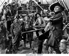 Errol Flynn as pirate Captain Peter Blood with his crew of fellow pirates.