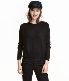 Black. Knit sweater in soft fabric with ribbing at neckline, cuffs, and hem. Slits at sides.