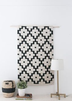 How to hop on the wall-textile bandwagon if you lack the patience for weaving (or the funds for a custom piece): stitch a loop for a dowel onto the back of a lightweight rug. #DIY