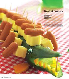 Leuk om te trakteren is deze krokodil van komkommer met kaas en knakworstjes. Benodigdheden: 1 komkommer cocktail prikkers kaasblokjes cocktailworstjes gele paprika Bereidingswijze: Neem de komkomm…