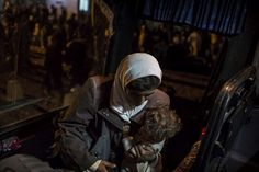 A newly arrived Syrian #refugee woman carries her child as she boards the bus that will take her to #Za'atri. ©UNHCR/O.Laban-Mattei