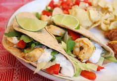 Tequila- Lime Shrimp Tacos w/ Chipotle Cream: garlic, sour cream, sauce, tequila, orange juice, shrimp, red bell pepper, flour tortillas, fresh cilantro, vegetable oil, ground cumin, salt, purple onion, chipotle chile, iceberg lettuce, shrimp, tequila, white sugar, sour cream, garlic, purple onion, chipotle chile, adobo sauce, ground cumin, salt, fresh cilantro, lime juice, vegetable oil, red bell pepper, purple onion, flour tortillas, iceberg lettuce, fresh cilantro
