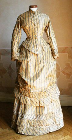 1883 front - Dress in three pieces (bodice, tablier and skirt) in silk taffeta with golden yellow striped green. ____ The bodice is closed at the front with 11 pearl buttons and 2 slightly different, and stiffened by 4 slats on the front. Waist bodice of about 60 cm. ____ (translated from Italian by Google)