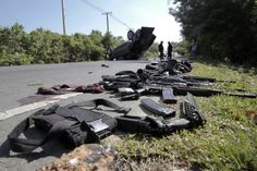 Gear and weapons of victims are placed by the road as security forces inspect the site of a bomb attack on police in the troubled southern province of Narathiwat March 30, 2014. REUTERS/Surapan Boonthanom