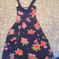 Floral hollister sundress Super cute navy blue sundress with pink flowers and hearts. Has two pockets near the bottom. Cute Ruffles on top with nice straps. Soft cotton. Only worn once. Love this but doesn't fit me anymore. Hollister Dresses Mini