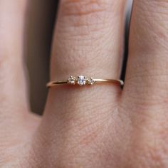 This petite diamond ring is a minimalist's dream come true. Featuring three white diamonds set in solid 14K yellow gold, this ring makes for the perfect wedding band or every day stacker. Solid 14K yellow goldOne 2mm center diamondTwo 1.3mm diamondsConflict-free diamonds 0.05KT total weight1mm th...