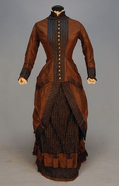 TAFFETA BUSTLE DRESS with BROCADE TRIM, c. 1880. 2-piece chestnut brown silk having long peplum bodice trimmed in brown and blue striped floral brocade, piped stand collar and cuff, brass buttons with cut steels, tiny pocket, skirt drawn to back away from front brocade panel with fancy box pleated ruffle, brown cotton lining. B-34, W-22, skirt L-39 1/2.