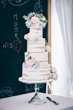 Pink and blue stunning semi naked wedding cake decorated with fresh flowers of hydrangea and roses with a buttercream coating in vanilla and strawberry, zesty lemon drizzle and salted caramel at Shilstone House  wedding venue perfect for a country garden wedding or rustic wedding